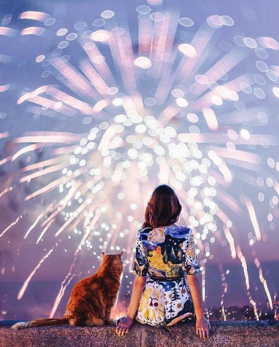 mujer con su gato viendo fuegos artiiciales