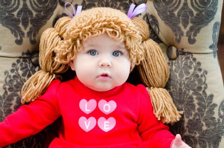 niña con traje rojo y peluca rubia de estambre
