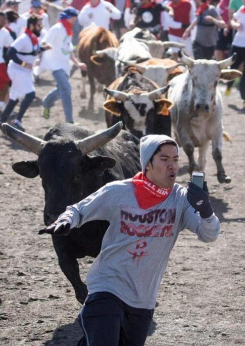 hombre se toma foto corriendo delante de un toro
