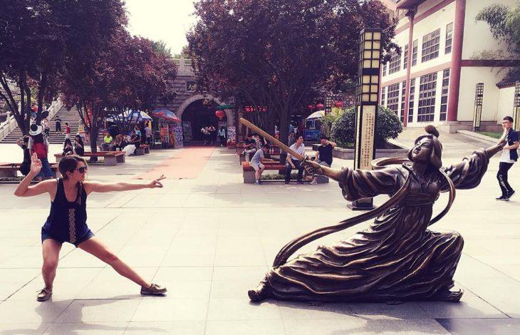 mujer posa al lado de una estatua de mujer oriental en posición de combate