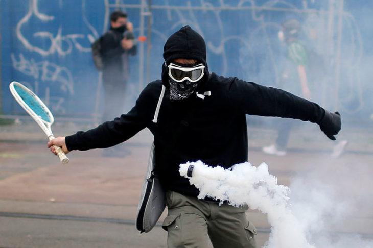 manifestante avienta un frasco de gas con una rqueta