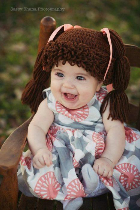 bebé con vestido y peluca castaña de estambre
