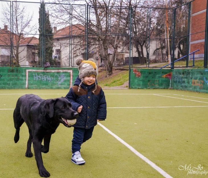 niño paseando a un perro negro