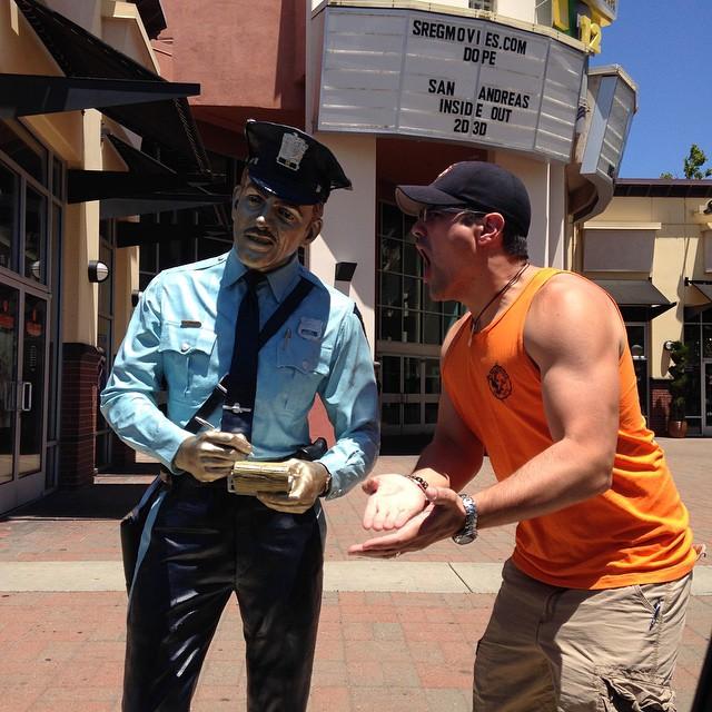 hombre posa al lado de la estatua de un oficial