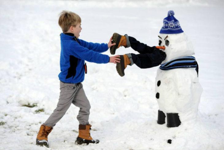 muñeco de nieve que parece que se comió a un niño mientras otro infante trata de sacarlo de su boca