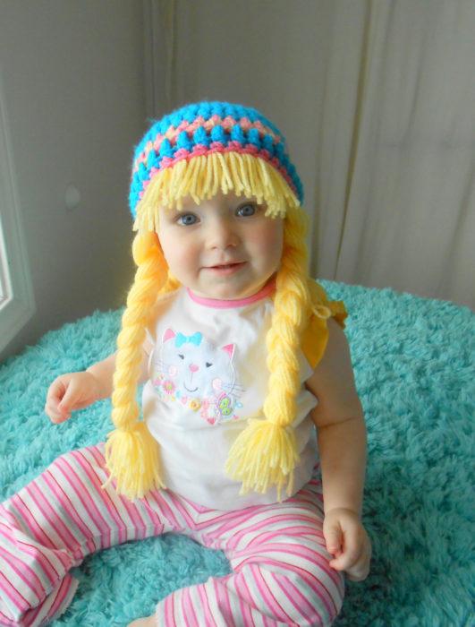 bebé con peluca trensaza rubia hecha de estambre