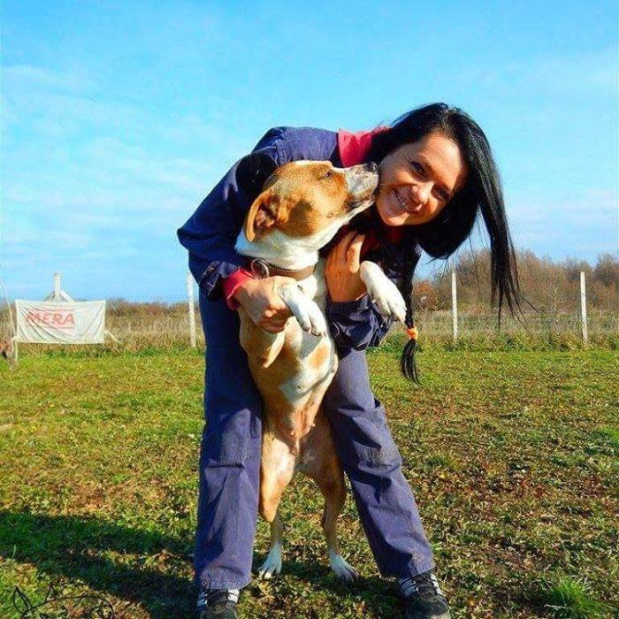 mujer feliz abrazando a un perro en un campo deportivo