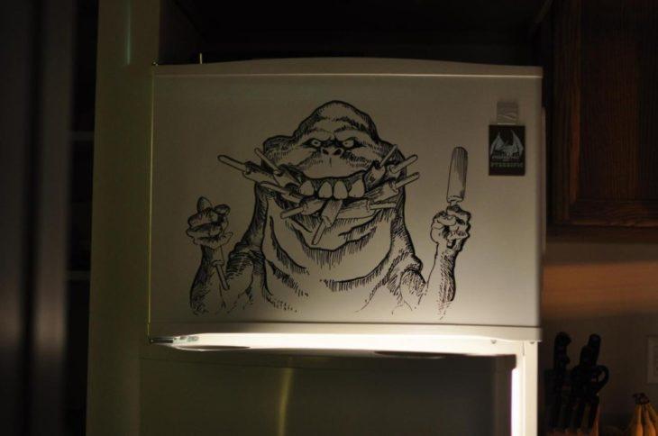 Dibujo de alguien comiendo hecho con plumón en un refrigerador