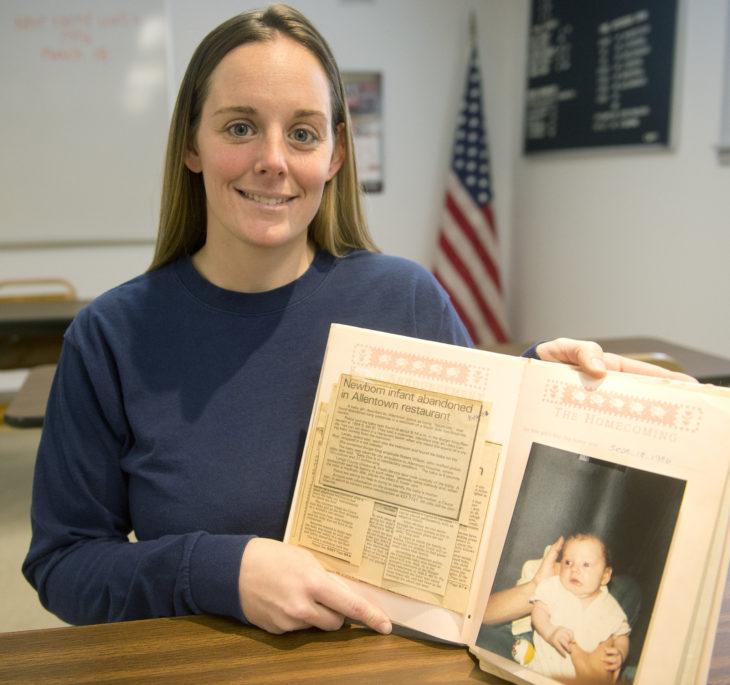 Mujer sosteniendo un album con su foto y la noticia de como su mamá la abandonó