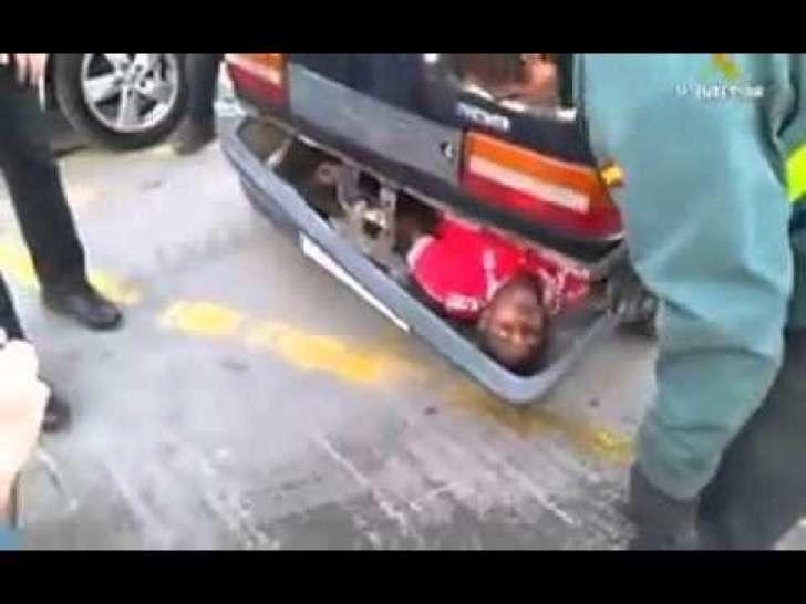 hombre escondido en el parachoques de un carro