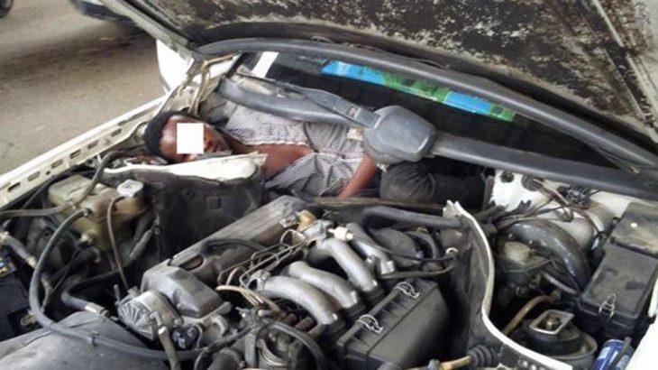 hombre escondido detrás del motor para cruzar la frontera