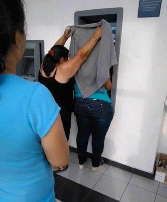 Mujer cubriendo el cajero con un sueter