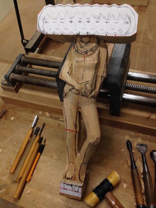 dibujo de una mujer con muchas caras pegado en madera