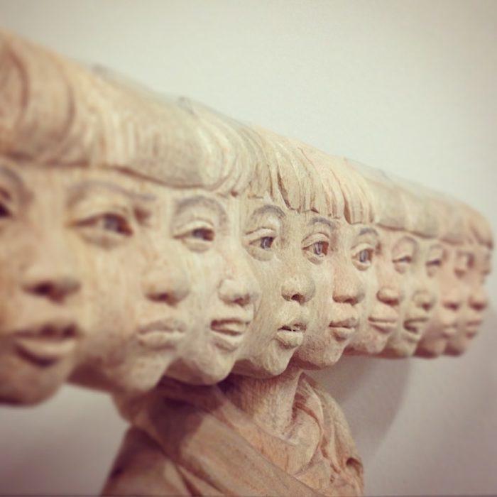 muchos rostros de mujer tallados en madera