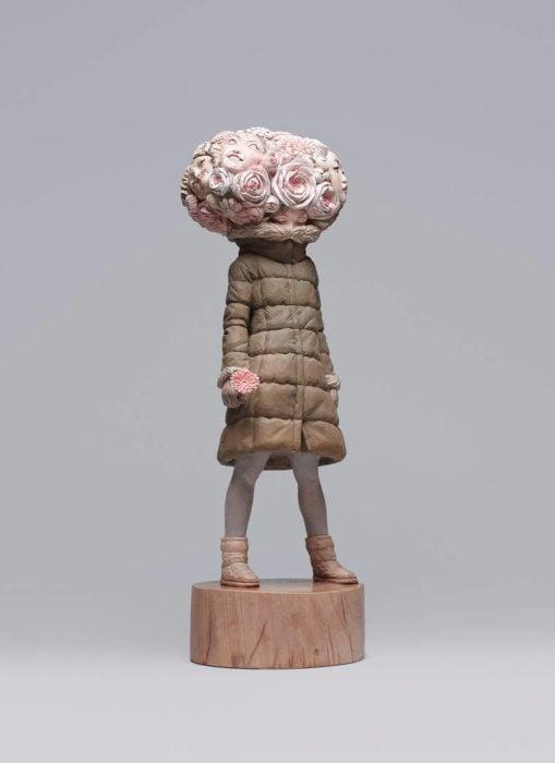 escultura de una mujer con rosas en la cabeza