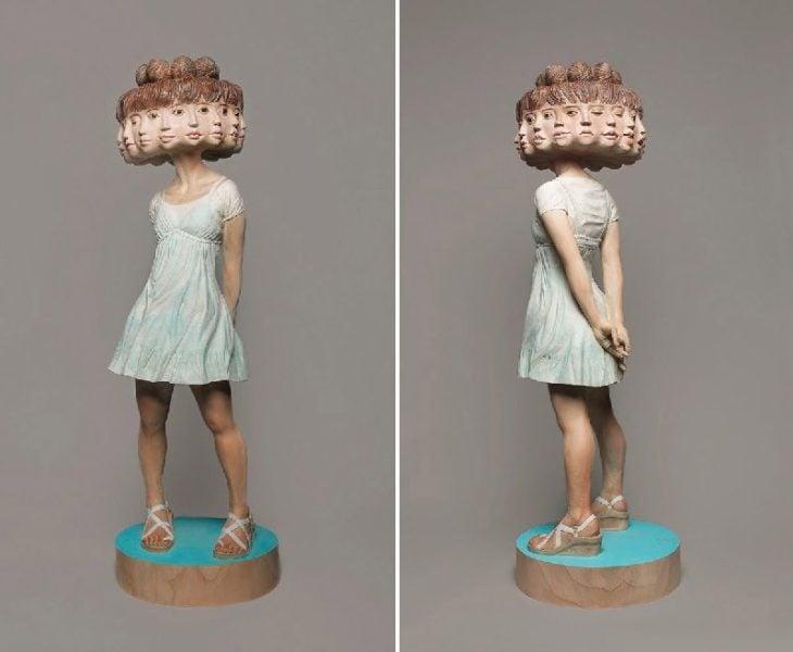 mujer con muchos rostros hecha de madera
