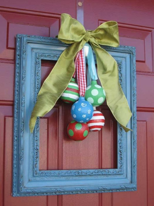 marco de madera con esferas y moño decoracion navideña en la puerta