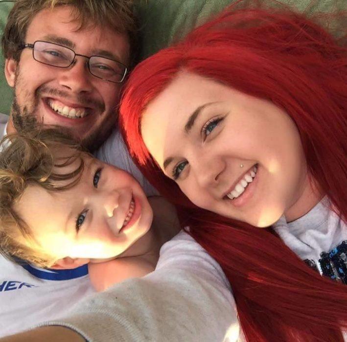 Mujer con cabello rojo junto con su esposo y su hijo