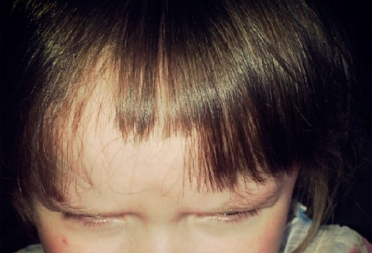 niña se corta el cabello a ella misma