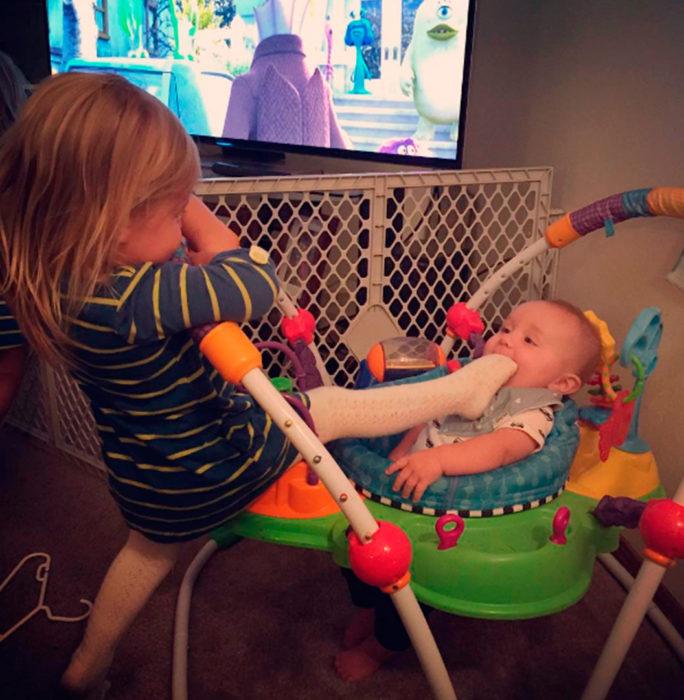niña calla a su hermano con el pie