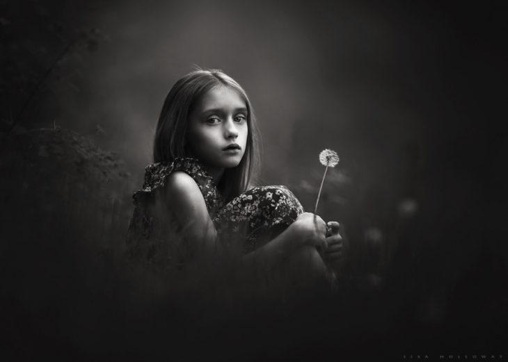 niña pasando con un diente de león con un manejo perfecto de la ilumiación por parte del fotografo