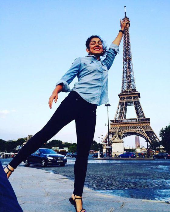 muchacha se toma foto con la Torre Eiffel