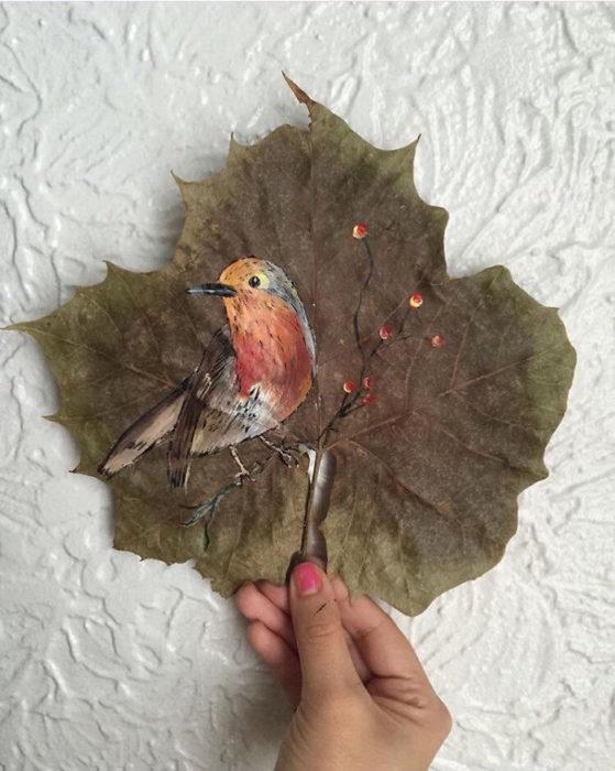pintura de un pájaro hecha sobre una hoja de árbol