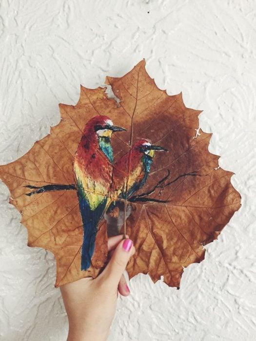pintura de dos pájaros posados sobre una rama