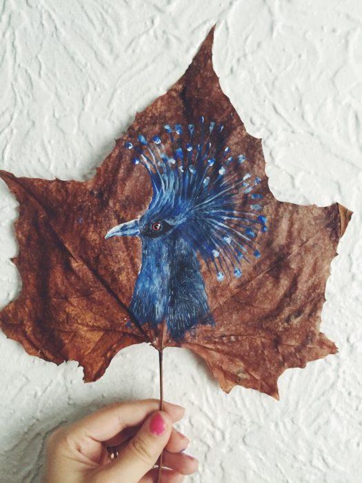 pintura de un ave hecha en la hoja de un árbol
