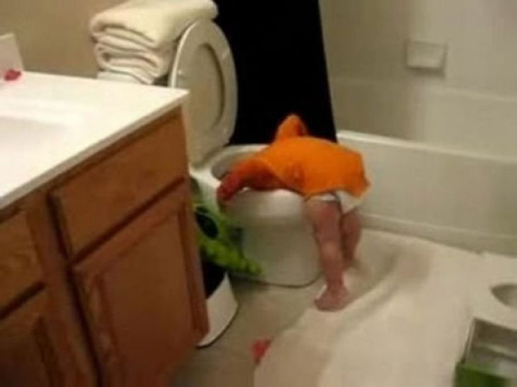 bebé con la cabeza en el inodoro