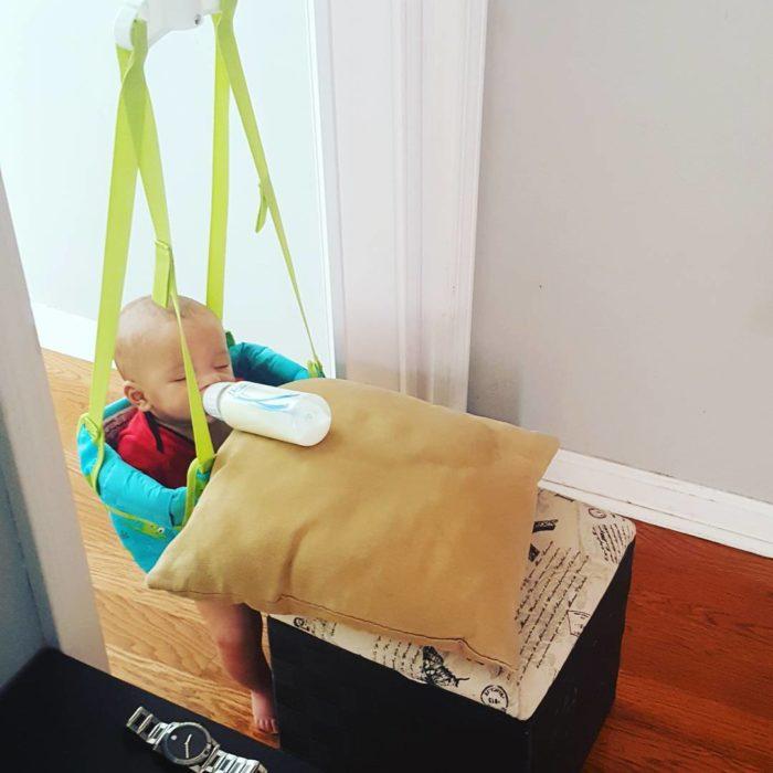 niño bebiendo de biberón sostenido por una almohada