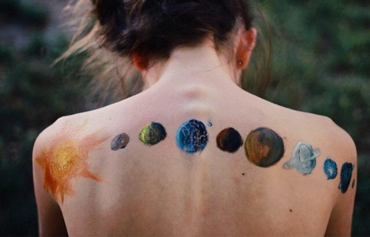 tatuaje de planetas en espalda de mujer