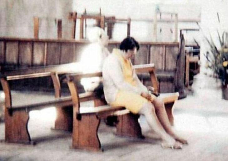 mujer orando en la iglesia con fantasma