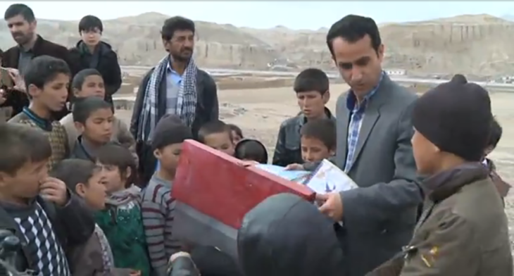 maestro de pakistan mostrando libros a sus alumnos
