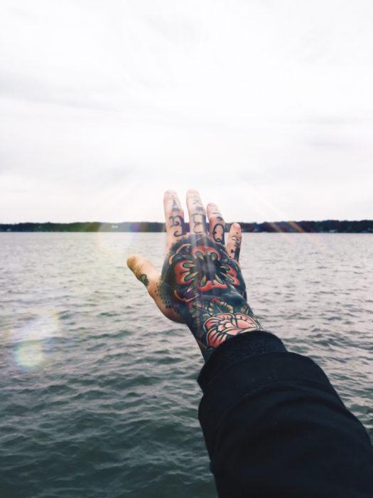 mano tatuada posa frente al mar