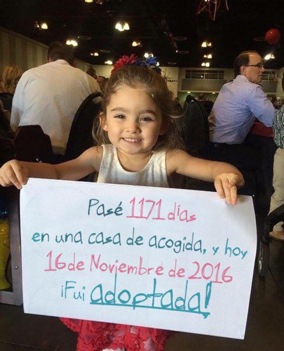 niña sosteniendo un cartel en el que dice que fue adoptada