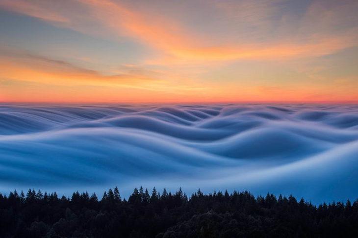 olas de niebla con el cielo anaranjado de fondo