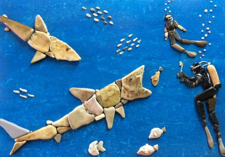 tiburones y buzos hechos con piedras de playa