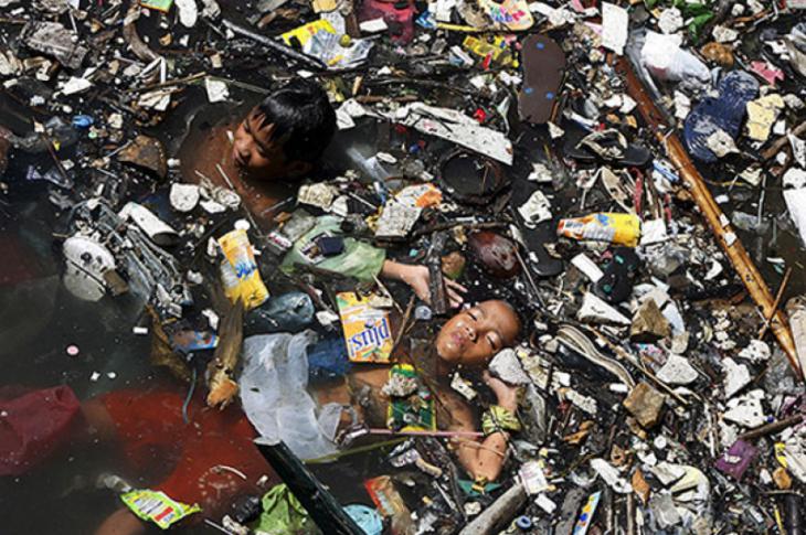 niños nadando en el mar lleno de basura