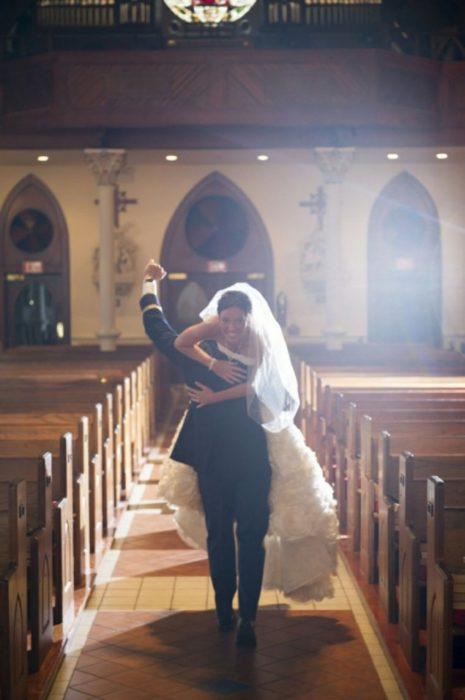 novio carga a la novia para fuera del altar
