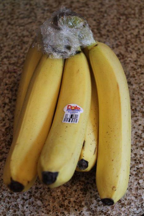 plátanos envueltos con plástico en la punta