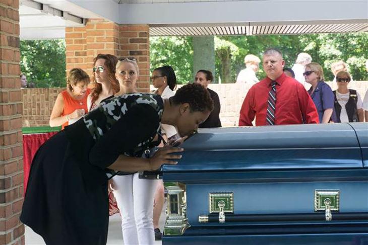mujer besa un ataúd en un funeral