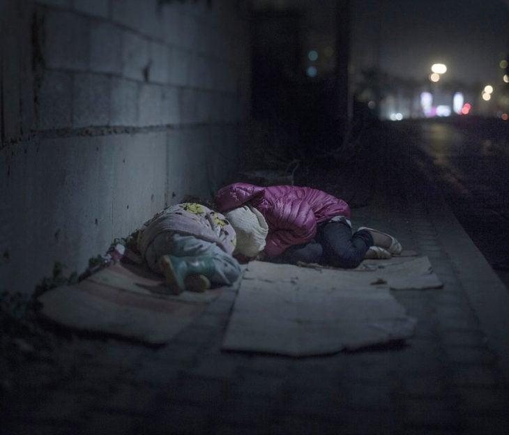 Dos niñas durmiendo sobre cartones en la calle
