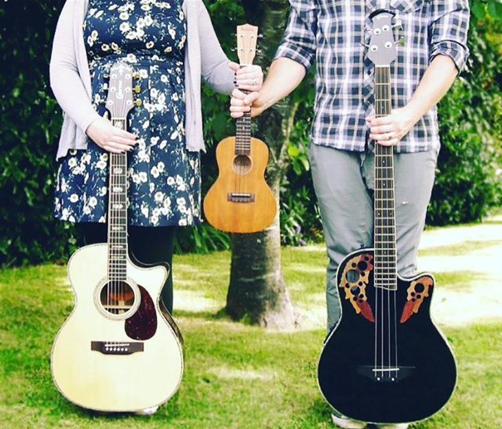 mujer y hombre sostienen en sus respectivas manos derechas guitarras y juntos con su mano izquierda una guitarrra pequeña