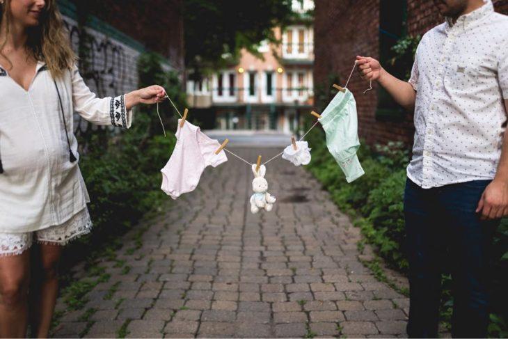 hombre y mujer sostiene ropa de bebé en un tendedero