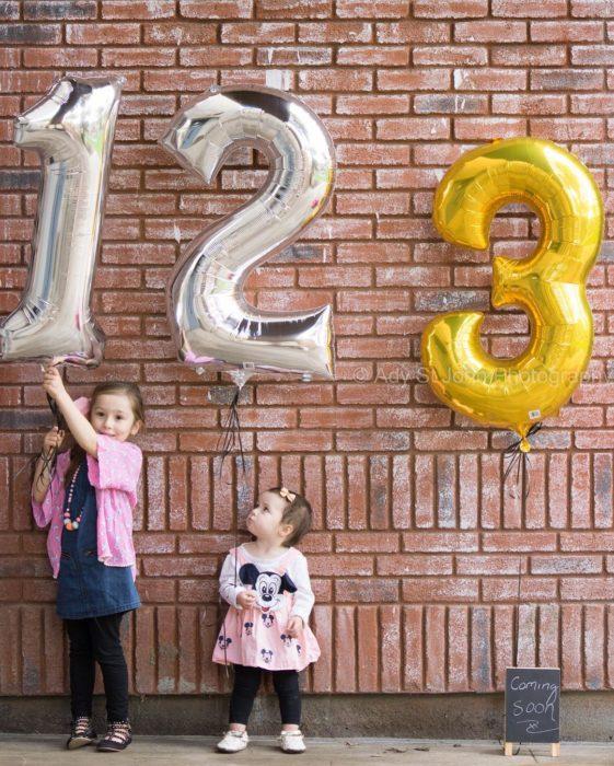 niñas sostienen globos para anunciar la llegada de un nuevo bebé