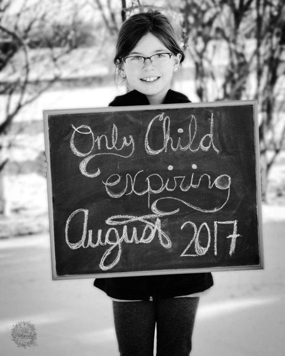 niña sostiene un pizarrón pequeño para anunciar que se convertirá en hermana mayor