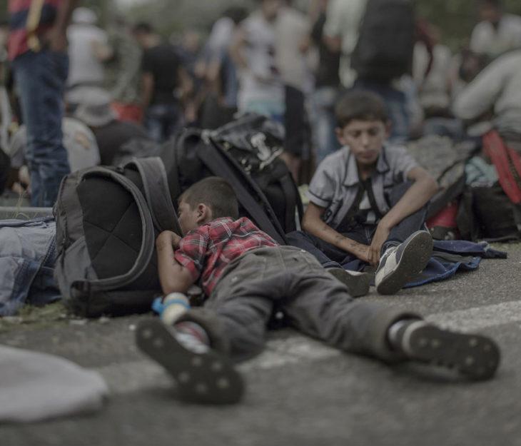 Niño sirio dormido sobre mochilas en medio de la calle
