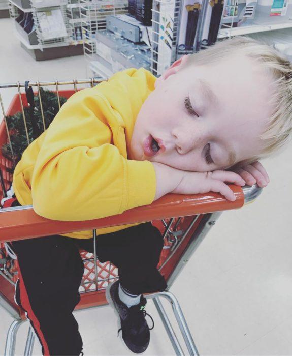 niño dormido en un carro de compras