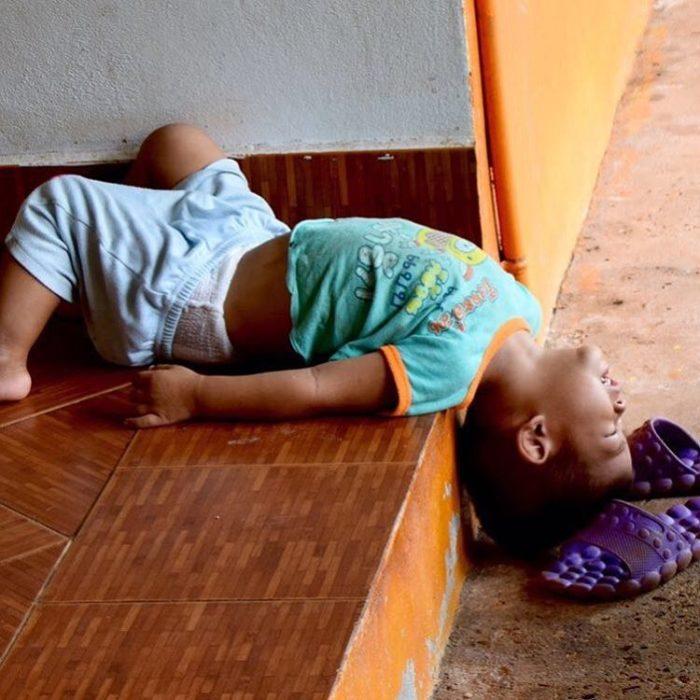 niño dormido de cabeza en las escaleras